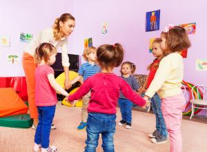 Children with early years provider playing in a circle