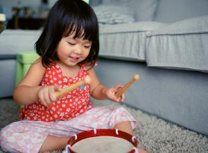 Little girl playing the drum