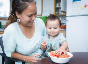 Mother with baby eating strawberries at a table.