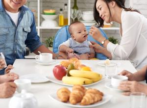 Child eating food with family at dinner table.