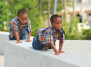 Two boys crawling along a ledge