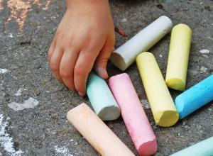 colourful chalk resting on the pavement. A child's hand reaching for one piece of chalk.
