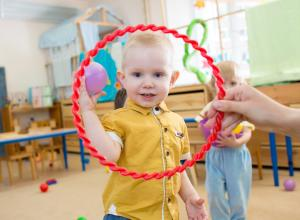 Child looking through hoola hoop that can be used to play Jack and Jill