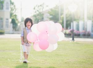Child with pink balloons