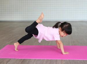 Child is on a pink yoga mat doing a yoga pose.