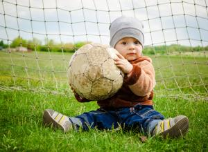 Child in front of net, holding a soccer ball.