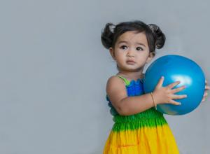 Child with blue ball in her hands.