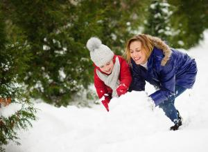 Child and caregiver making a snow boulder.