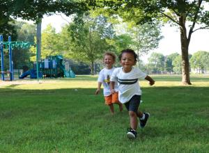Two children running outside on grass.