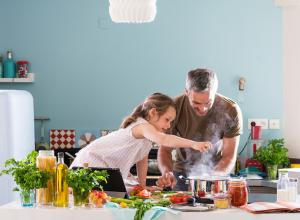 Parent making meal with daughter