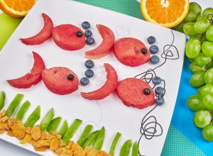 Fish made out of fruit on a white plate.