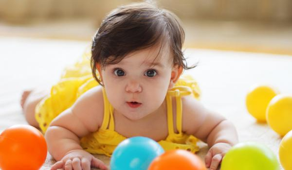 Infant girl crawling after balls