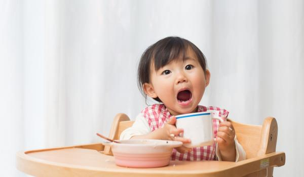 Child eating food and showing teeth