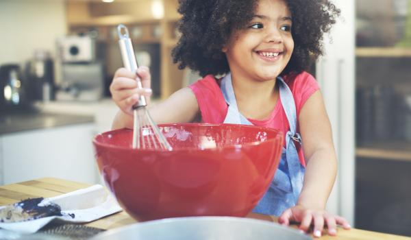 Girl stirring baking ingredients in a red bowl.