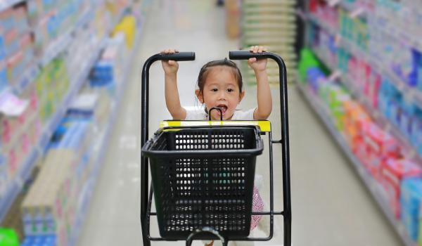 Child pushing grocery cart in aisle.