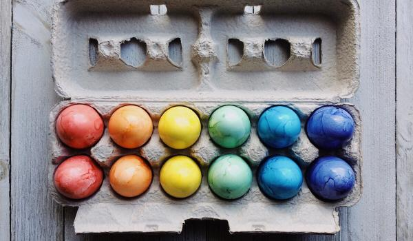 Coloured eggs in an egg carton.