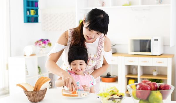 Parent and child cooking together.