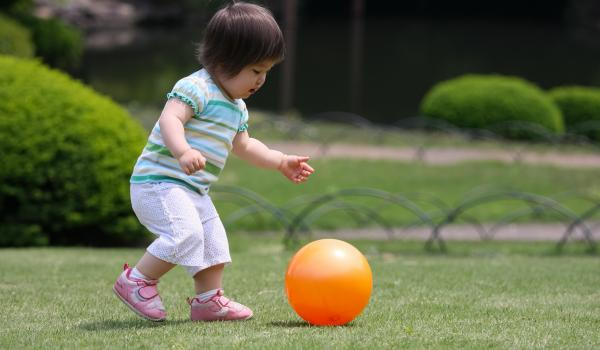 Little girl running and kicking ball in park.