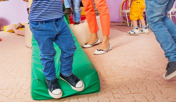 Children running inside in a designated play space.
