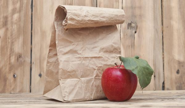Paper bag on a desk with an apple beside it.
