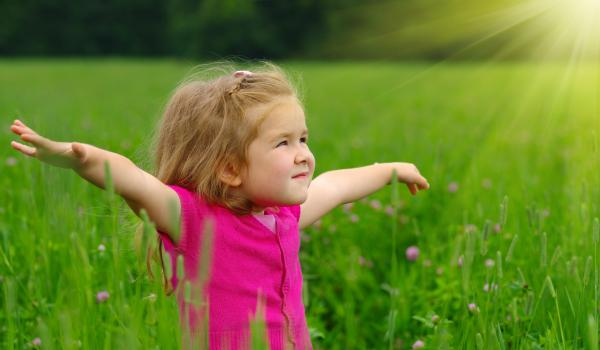 Child stretching out arms to the side, standing in grass.