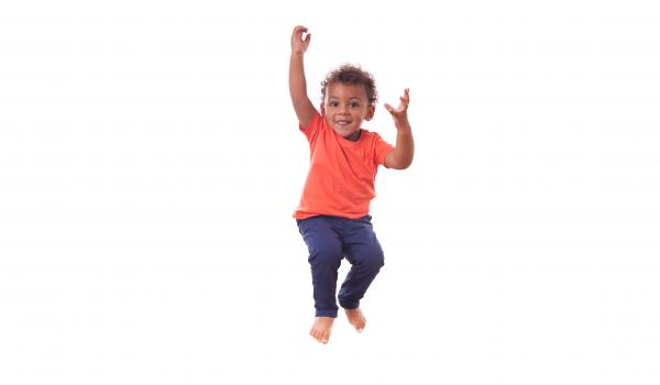 Child jumping in the air and twisting.