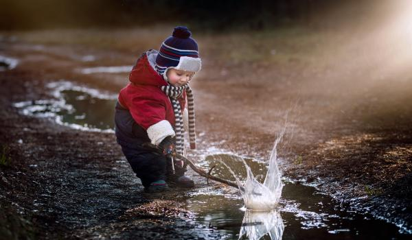 Child playing in puddle.