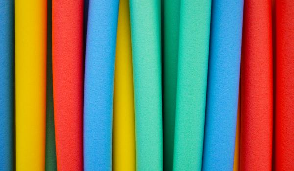 Colourful pool noodles that could be used for obstacle course game.