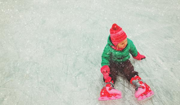 Child on ice rink wearing skates