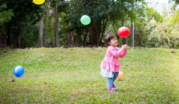 A small child is outside and playing with balloons.