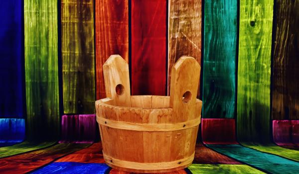 Wooden bucket on colourful panels.