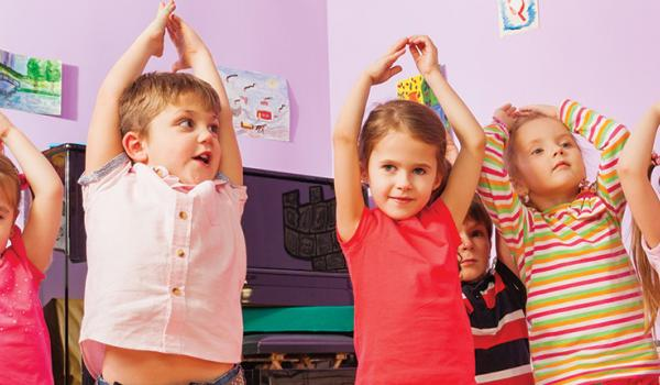 A group of children all reaching over their heads as though stretching