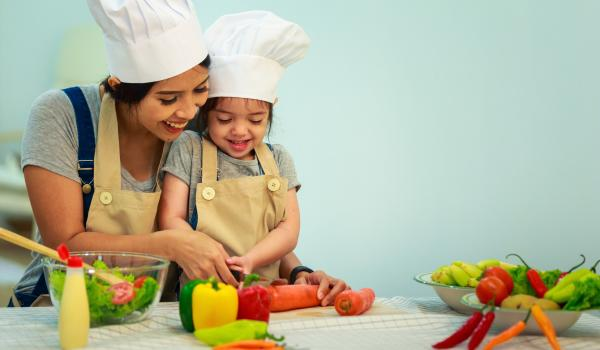 Parent and child cutting vegetables in kitchen.