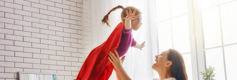 Girl with superhero cape jumping in to mothers arms