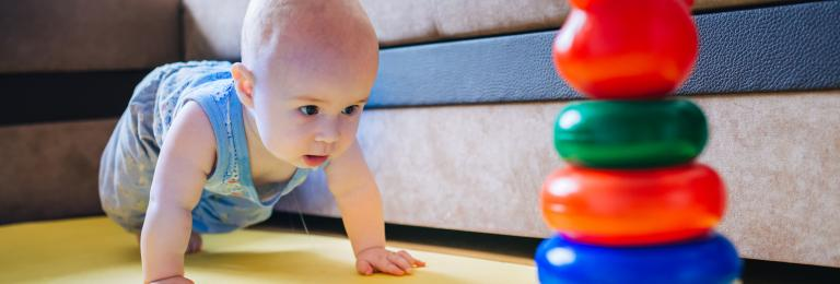 Infant crawling towards toy