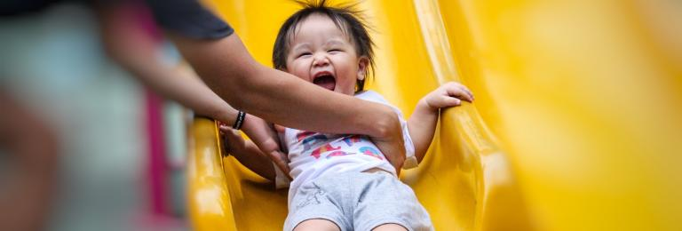 Parent catching smiling child at the end of a slide