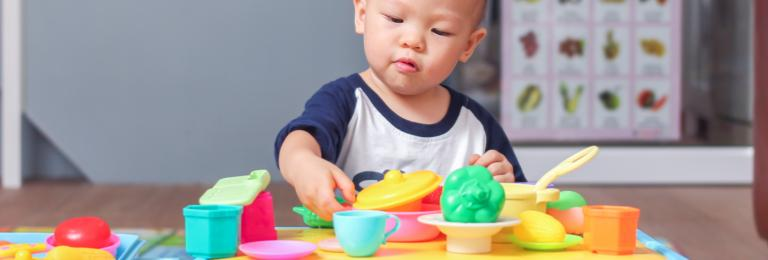 Infant playing with plastic food