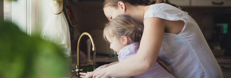 Child washing hands with caregiver.