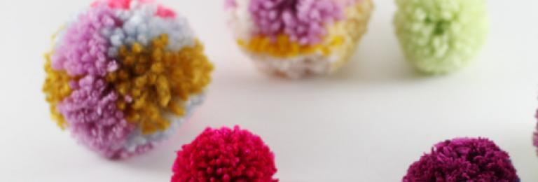 Colourful pom poms  on white surface