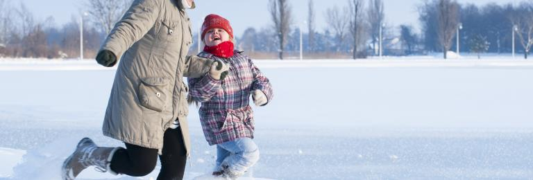Adult and child running in the snow.