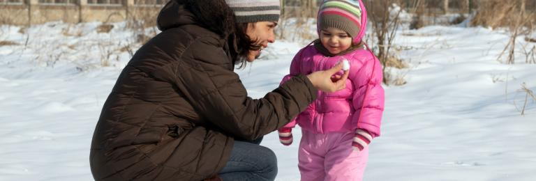 Child playing in snow with caregiver.